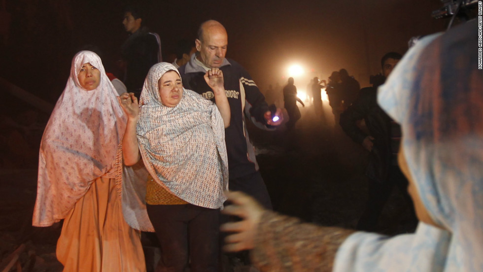 Palestinian civilians leave their houses following an Israeli airstrike.