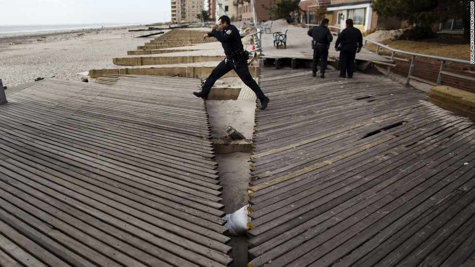 A New York police officer jumps over a large crack in a boardwalk in Brooklyn on Wednesday, November 14. The boardwalk was damaged by the storm surge from Hurricane Sandy.