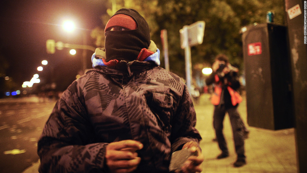 A protester holds a stone during clashes with police Wednesday in Madrid.
