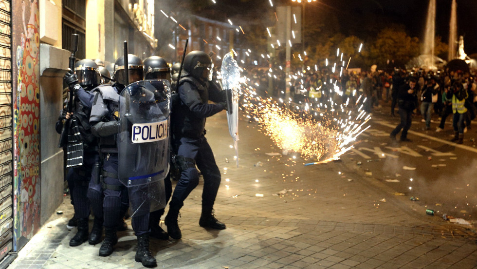 Police officers protect themselves from a projectile at the end of a protest Wednesday near Spain's parliament building in Madrid.