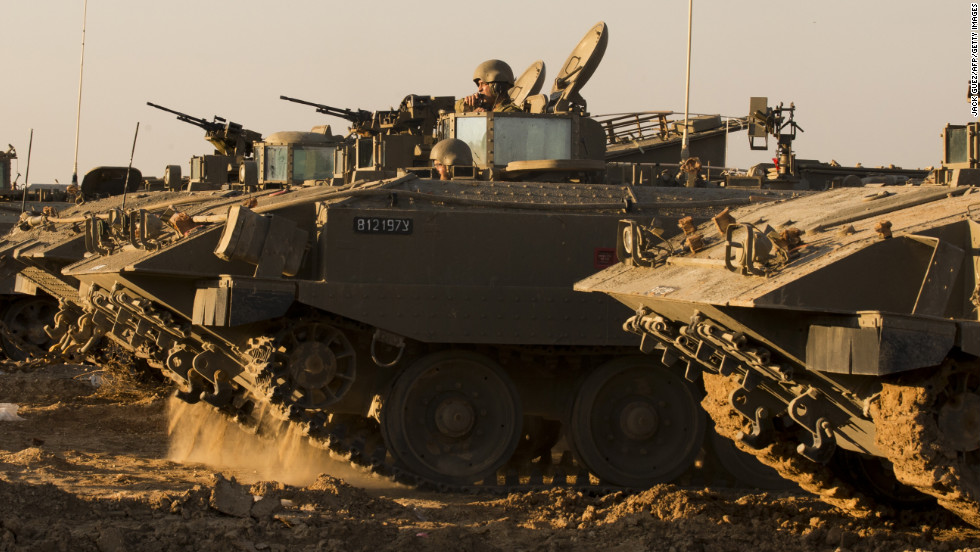 Israeli soldiers rest by their armored personnel carriers stationed on the Israel-Gaza border on Thursday, November 15.