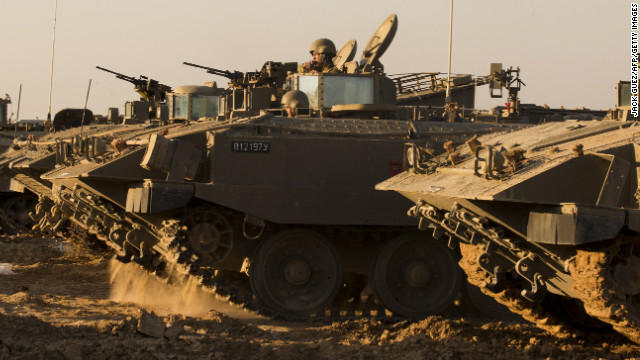 Israeli soldiers rest by their armored personnel carriers (APC) stationed on the Israel-Gaza border on Thursday.