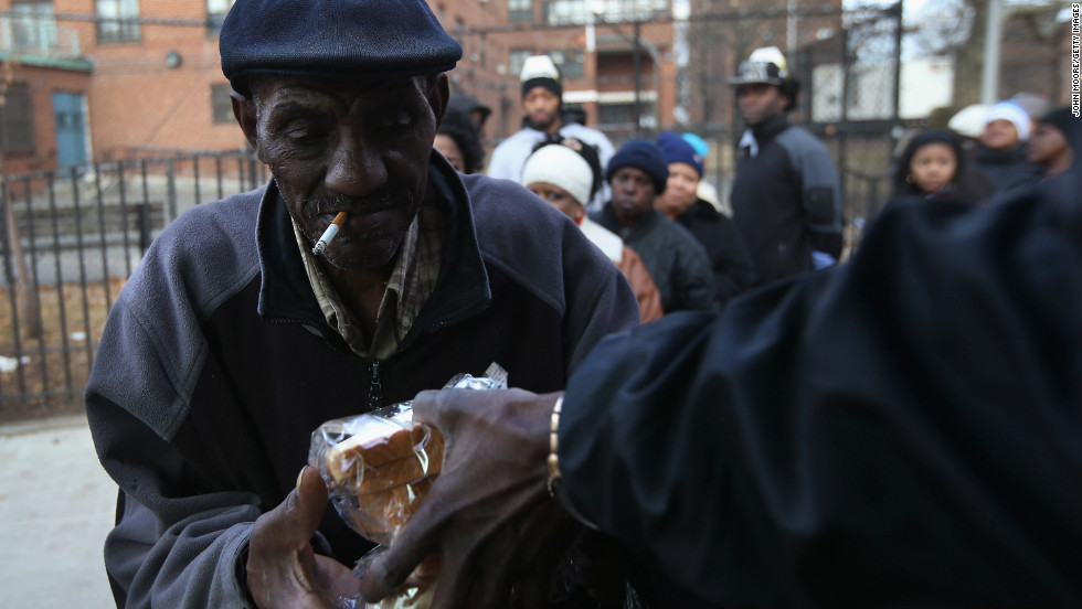 People receive free sandwiches from a mobile food distribution center in the Rockaway neighborhood of Queens, New York, on Thursday.