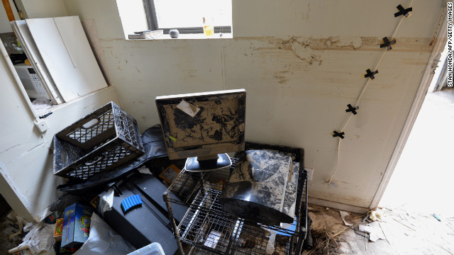 Muddy debris is piled in an apartment Wednesday in Rockaway, Queens, New York, where the high-water mark is visible on the walls.