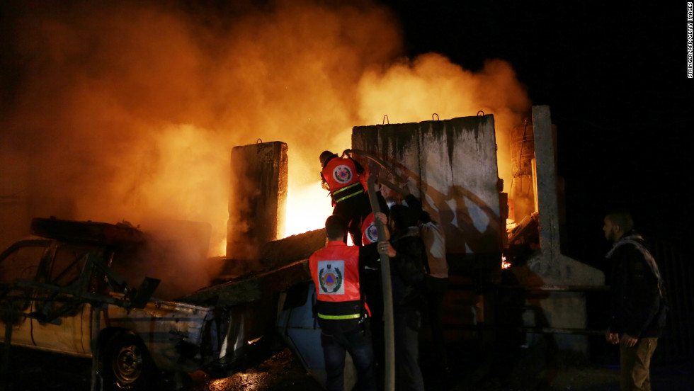 Palestinians extinguish a fire after Israeli air strikes targeted an electricity generator that fed the house of Hamas's Prime Minister Ismail Haniyeh in Gaza City, on Thursday, November 15.