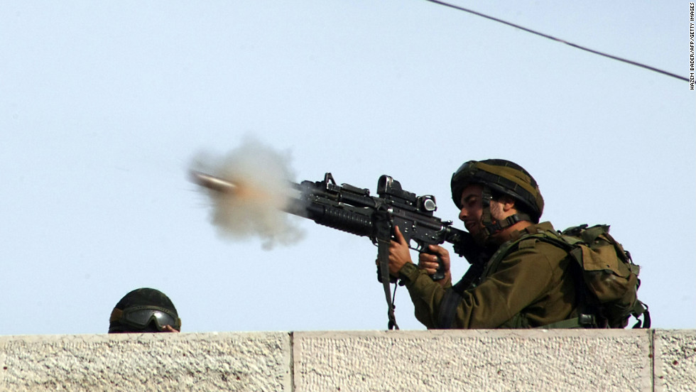 An Israeli soldier fires a tear gas canister toward Palestinian stone throwers on a road mainly used by Israeli settlers in the West Bank village of Beit Omar on Friday, November 16.