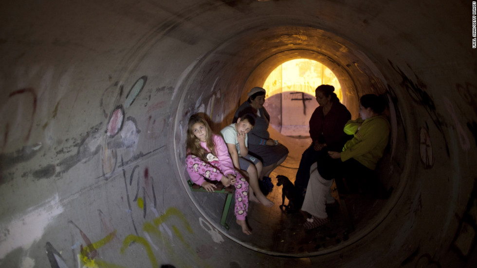 Israelis take cover in a pipe used as a bomb shelter, after a rocket was launched from the Gaza Strip on Thursday, November 15, in Kiryat Malachi, Israel.