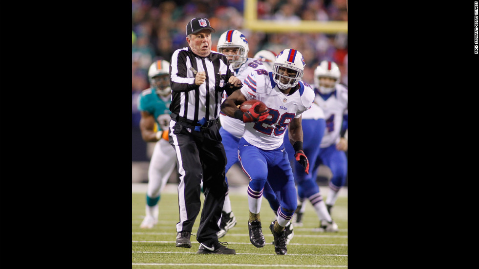 Buffalo's C.J. Spiller bumps umpire Jeff Rice on a run against the Miami Dolphins.