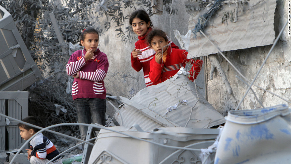 Palestinian children look at damaged buildings following Israeli air strikes Sunday, November 18, in Rafah.