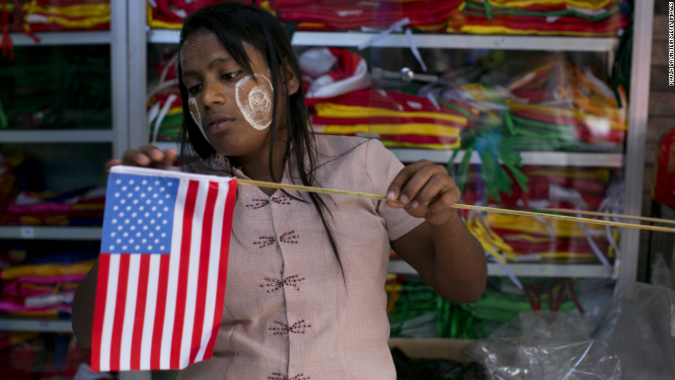 A Burmese woman fixes an American flag onto a wooden stick at a flag shop in Yangon on Sunday.