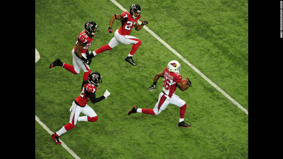 LaRod Stephens-Howling of the Cardinals carries the ball against No. 22 Asante Samuel, No. 25 William Moore and No. 27 Robert McClain of the Falcons on Sunday.