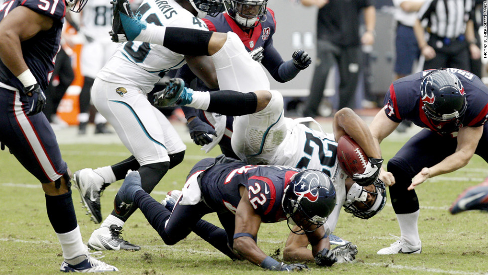 Rashad Jennings of the Jaguars is upended by Alan Ball of the Texans on Sunday.