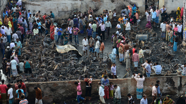 Onlookers gather around the wreckage of fire-damaged rickshaws in a slum in Dhaka, Bangladesh, on Sunday.