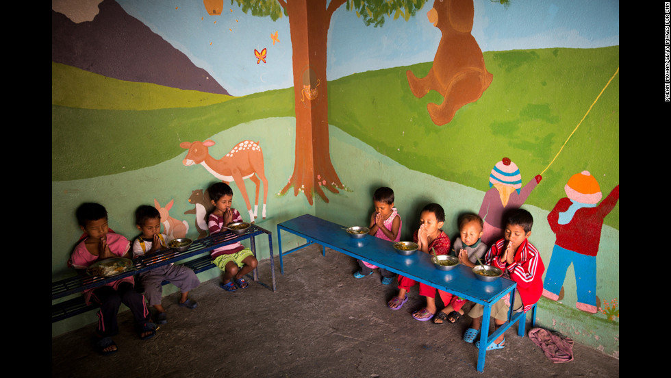 Children at the Butterfly Home say a prayer before eating lunch. Dozens of children live at the home with Basnet and some of her staff members.