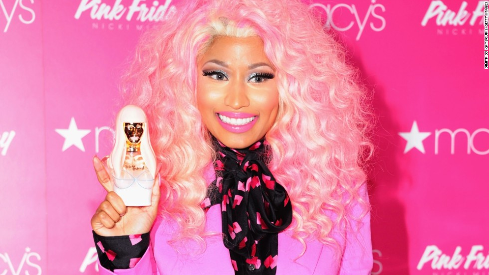 "Nicki Minaj is all smiles as she shows off the bottle of her new fragrance, ""Pink Friday,"" at the fragrance launch in New York on November 20."
