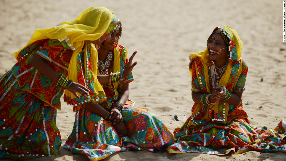 Young Indian women dressed in traditional Rajasthani clothing laugh while they wait for the start of a traditional dance presentation on Wednesday.