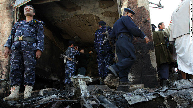 Yemeni troops inspect the scene where a military plane crashed in Sanaa on November 21, 2012.