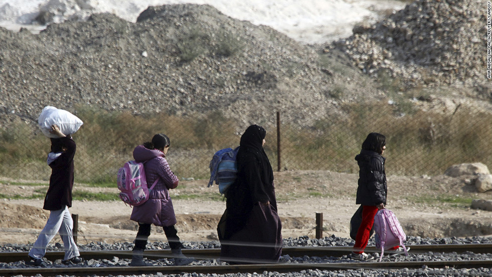 Syrian refugees fleeing their homes in the northern Syrian town of Ras al-Ain walk to cross the border fence into Turkey, as seen from the Turkish border town of Ceylanpinar, on Wednesday, November 21.