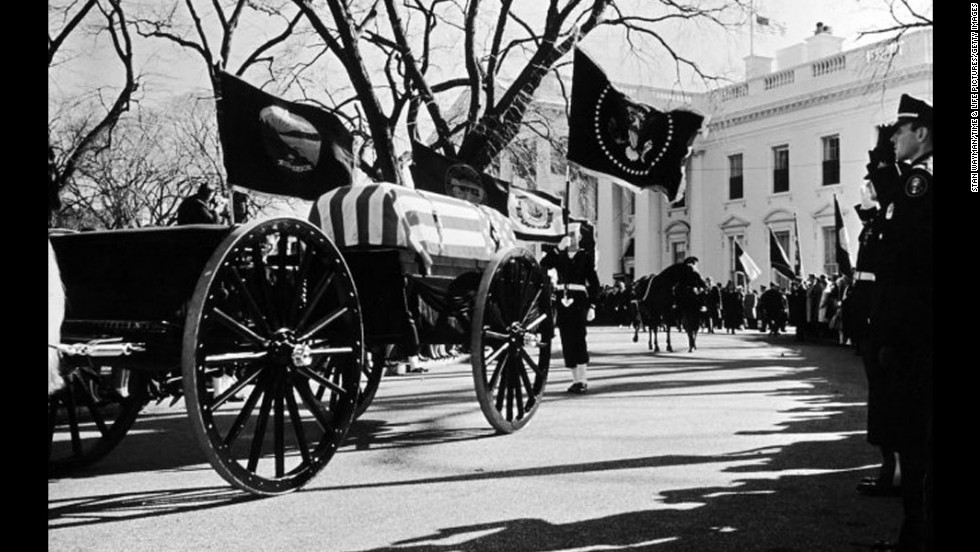 John F. Kennedy's flag-draped casket lies in state in Washington.