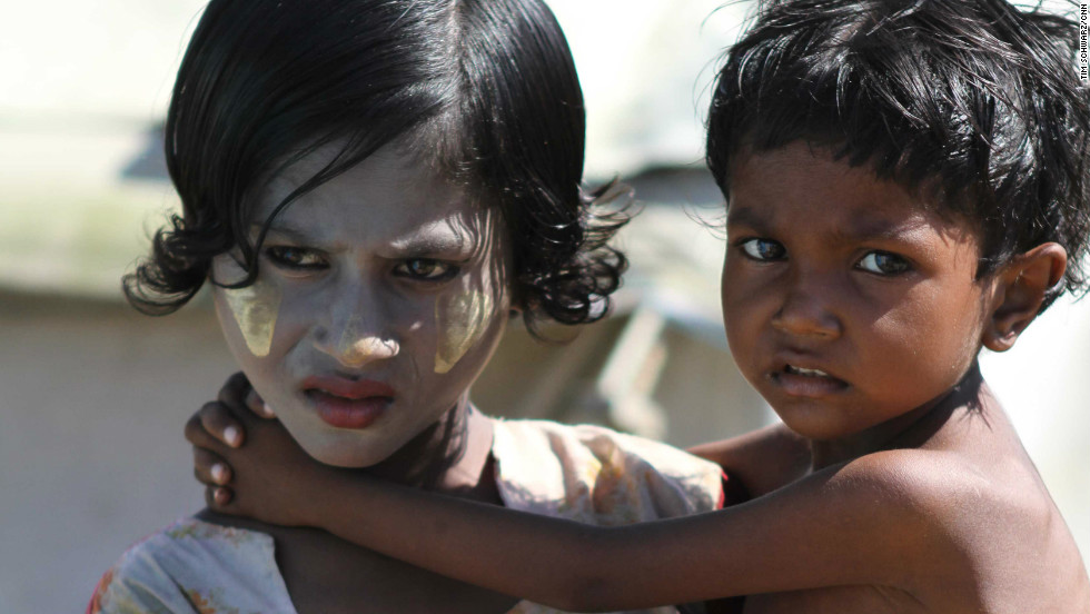 "A girl wearing ""thanaka"" on her face carries her brother. The traditional cosmetic made form tree bark is used as sunscreen, insect repellent and antiseptic. After nearly half a year in the camps doctors are afraid more an more children are at risk of acute malnutrition."