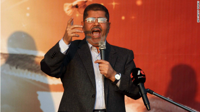 President Mohamed Morsy waves to his supporters in front of the presidential palace in Cairo on November 23, 2012.