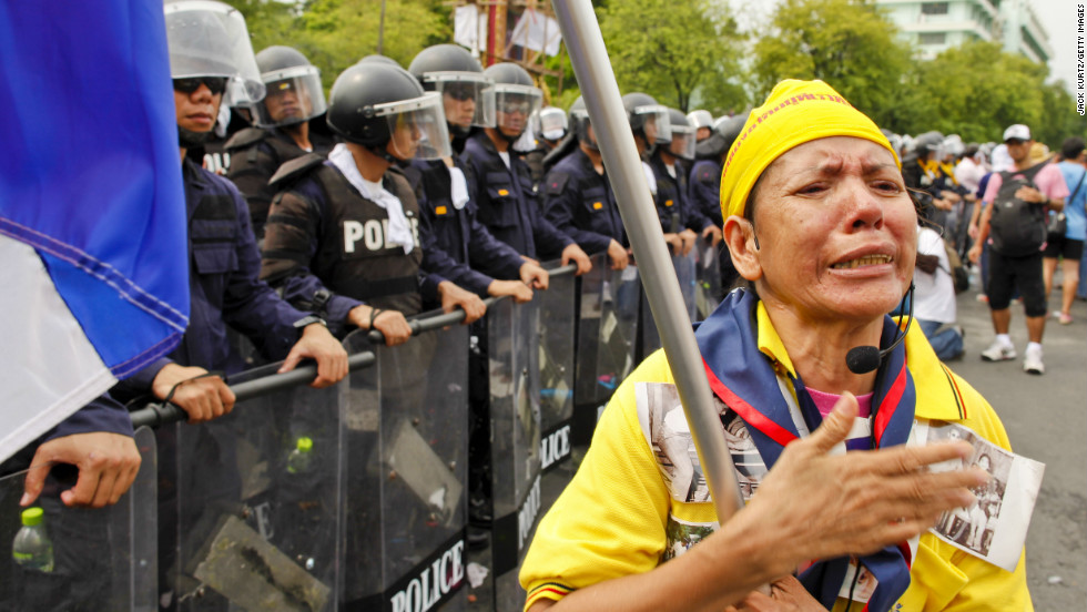 A Thai woman professes her love for Bhumibol Adulyadej, the king of Thailand, in front of riot police Saturday.