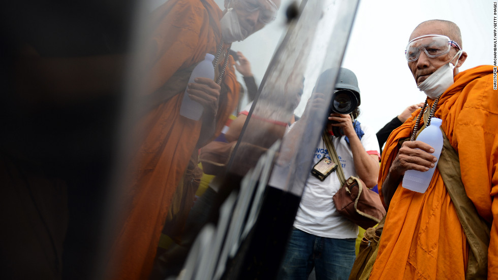 A Thai Buddhist monk is reflected in a riot police officer's shield as he takes part in an anti-government protest on Saturday.
