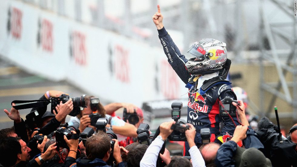 Sebastian Vettel celebrates after securing his third consecutive Formula One title. The Red Bull racer claimed a sixth place finish at the Brazilian Grand Prix to win the championship by three points from Fernando Alonso.