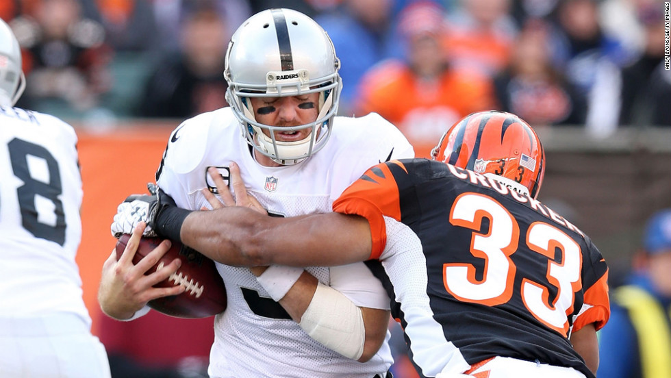 Carson Palmer of the Raiders is hit by Chris Crocker of the Bengals on Sunday.