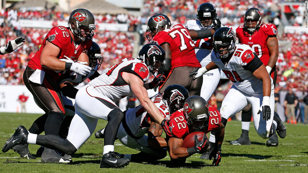 Running back Doug Martin of the Buccaneers dives for extra yardage as defender Robert McClain of the Falcons brings him down on Sunday.