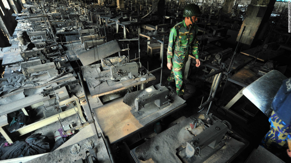A Bangladeshi army staffer walks through rows of charred sewing machines on November 25.