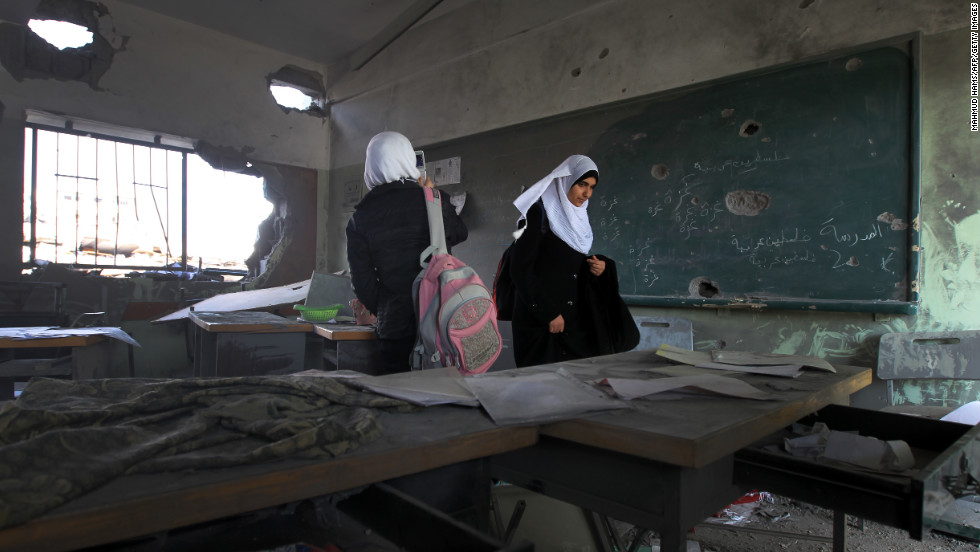 Palestinian school girls walk in a destroyed class room on Monday, November 26, in Gaza. The school was damaged some days ago, before a truce between Hamas and Israel.