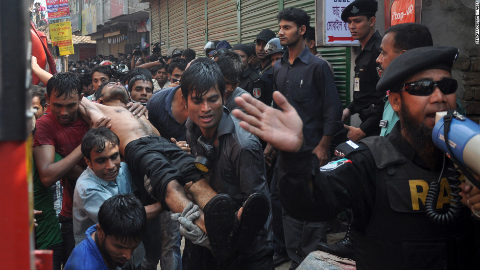 Bangladeshi firefighters carry an injured man from the fire on November 26.
