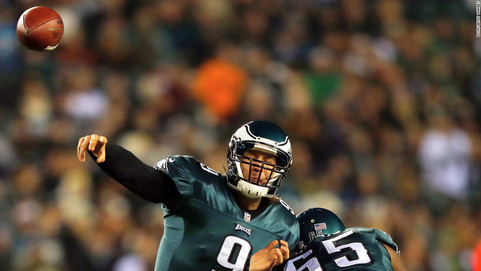 Eagles quarterback Nick Foles passes the ball as teammate King Dunlap blocks in the first quarter against the Carolina Panthers.