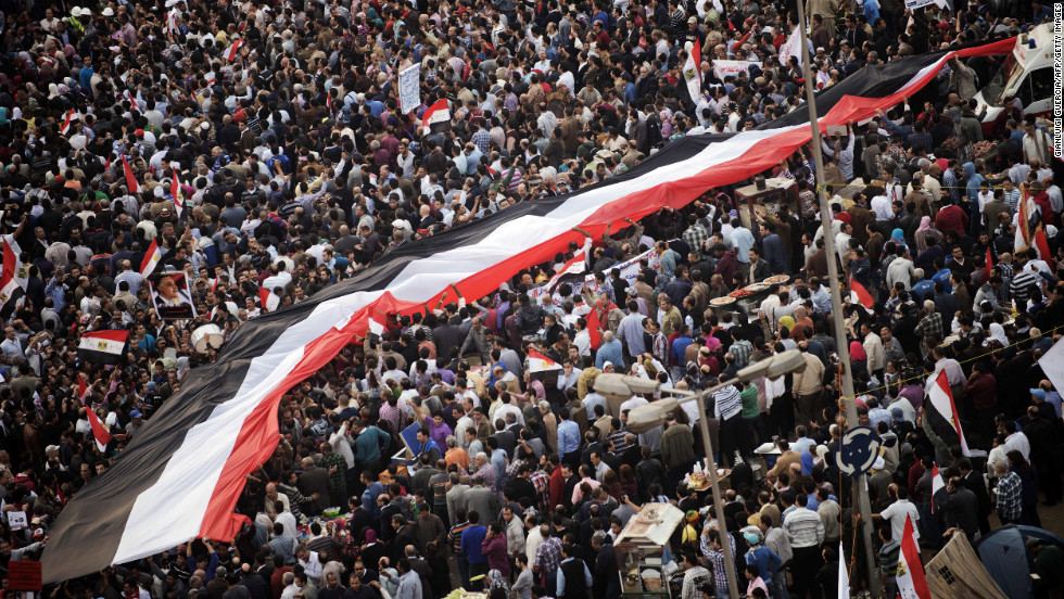 Egyptians carry a giant national flag as tens of thousands take part in a mass rally in Cairo on Tuesday, November 27, against a decree by President Mohamed Morsy granting himself broad powers.