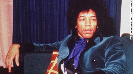 American rock musician Jimi Hendrix (1942 - 1970) wears a teal velvet suit while reclining on a sofa.