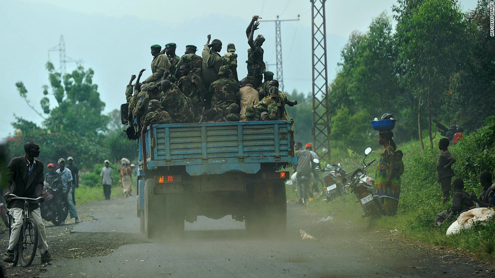Fighters from the M23 rebel movement ride on the back of a truck, passing a camp for the internally displaced in Mugunga, Democratic Republic of Congo on November 24, 2012.