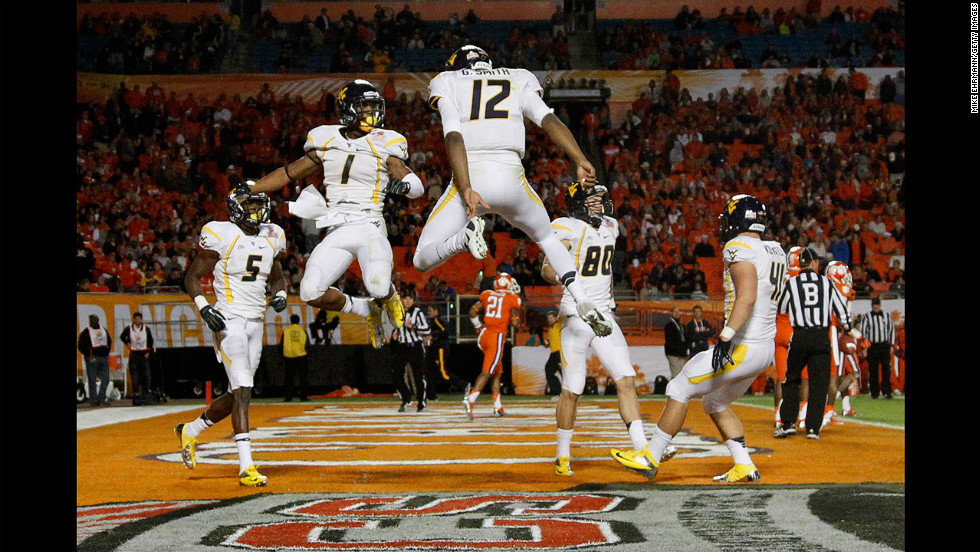 No. 1 Tavon Austin and No. 12 Geno Smith of the West Virginia Mountaineers celebrate after Austin caught a 37-yard touchdown reception thrown by Smith in the third quarter against the Clemson Tigers during the Discover Orange Bowl on January 4 in Miami Gardens, Florida. The Mountaineers won 70-33.
