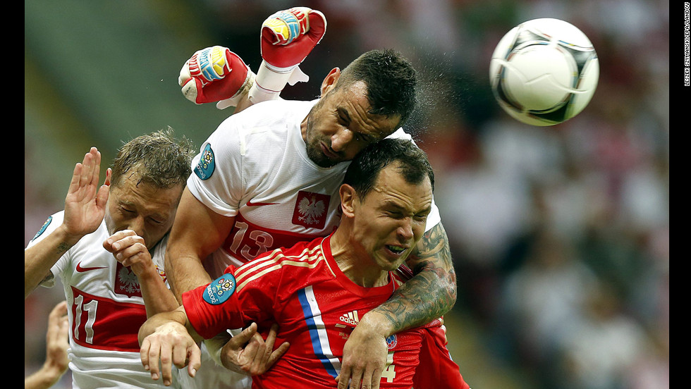 From left, Rafal Murawski and Marcin Wasilewski of Poland vie for the ball with Sergei Ignashevich of Russia during the Group A preliminary round match of the UEFA EURO 2012 between Poland and Russia in Warsaw, Poland, on June 12.