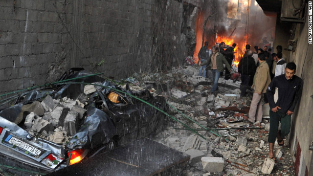 Syrian men inspect the scene of a car bomb explosion in Jaramana, a mainly Christian and Druze suburb of Damascus, on November 28, 2012. At least two car bombs exploded in Damascus killing and injureing a numbe of people. AFP PHOTO/STR         (Photo credit should read STR/AFP/Getty Images)