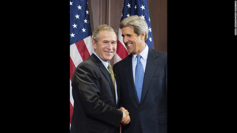President George W. Bush shakes hands with 2004 rival Sen. John Kerry, D-Massachusetts, a year after the election at a ceremony for Bush to sign a bill that Kerry co-sponsored.