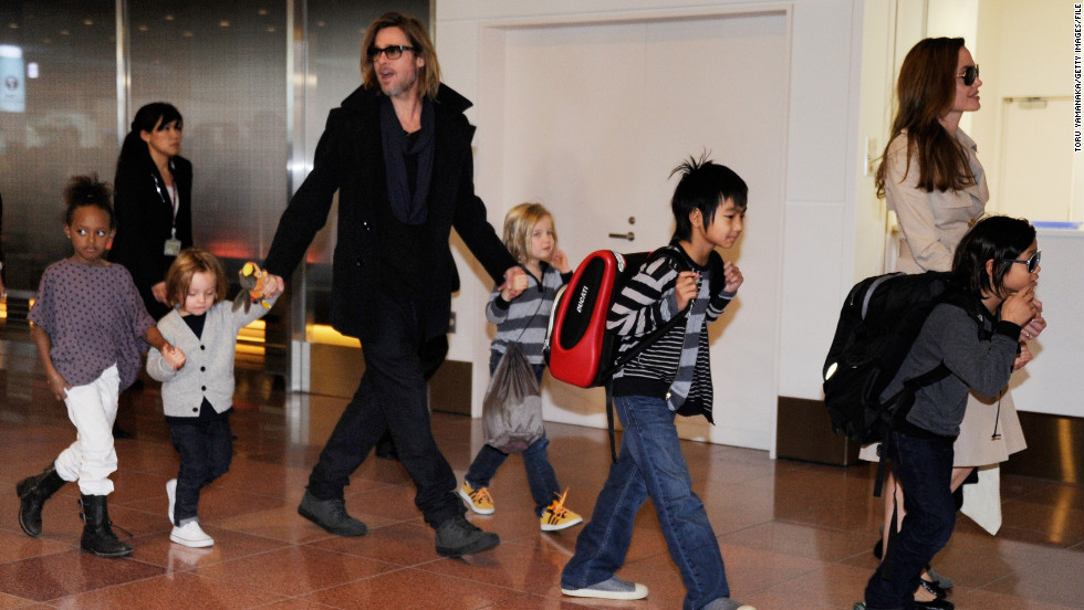 "Every so often, photographers will catch the entire Jolie-Pitt clan all at once, which is what happened here as the family arrives at the Haneda Airport in Tokyo in November 2011. They were in town to promote Pitt's film ""Moneyball,"" which earned him another Oscar nomination, his third for acting."