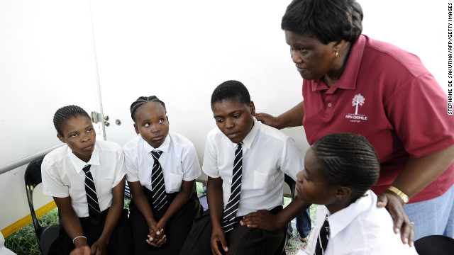 Students listen to a a health counselor talking about HIV and AIDS prevention in a mobile clinic at a high school in South Africa.