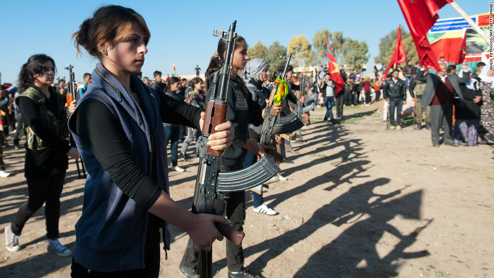 Syrian-Kurdish women and members of the Popular Protection Units, an armed opposition group to the Syrian government, stand guard during a comrade's funeral in a northern Syrian border village on December 1.