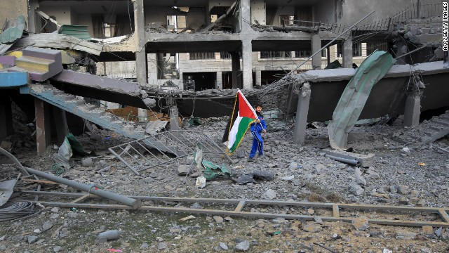 A Palestinian boy carries the national flag as he makes his way through the debris of the destroyed Palestine Stadium.