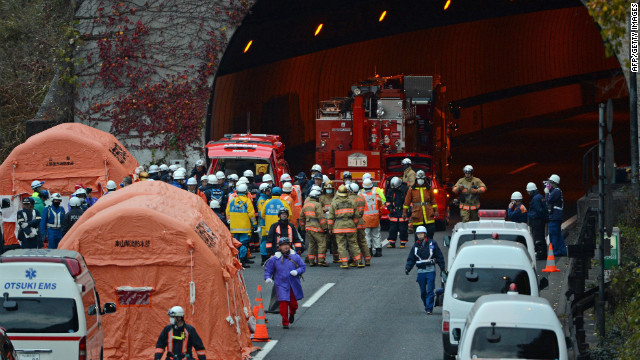 Rescue workers and police gather outside the Sasago tunnel along the Chuo highway near the city of Otsuki in Yamanashi prefecture, 80 kms west of Tokyo on December 2, 2012 after part of the tunnel collapsed. Japanese rescuers found several charred bodies in the highway tunnel that collapsed early in the day, crushing cars and triggering a blaze, and sparking fears of another cave-in.