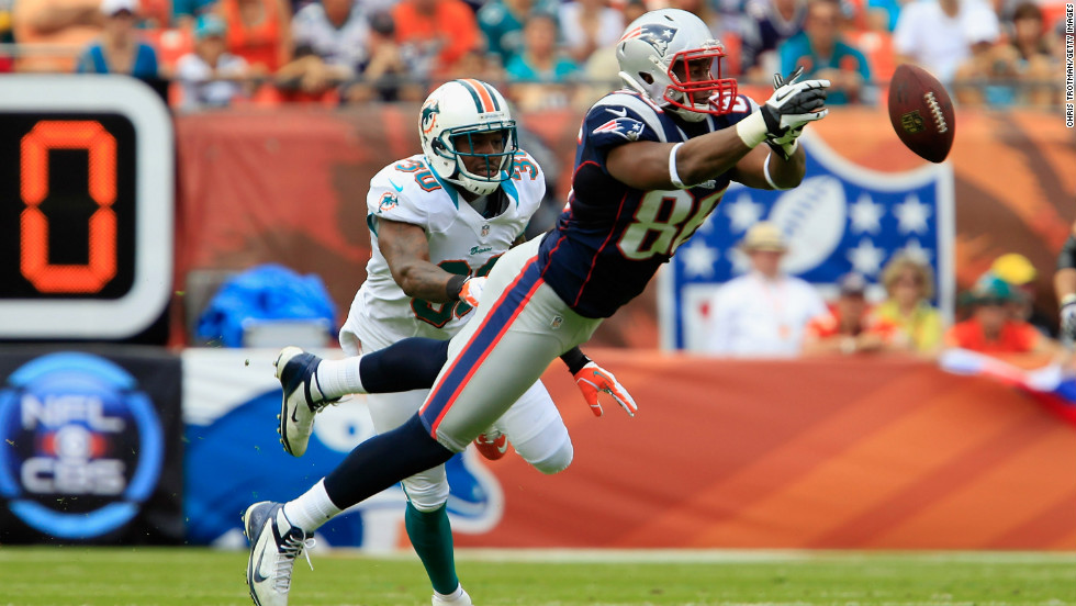 Tight end Daniel Fells of the New England Patriots misses a catch as strong safety Chris Clemons of the Miami Dolphins looks on Sunday.