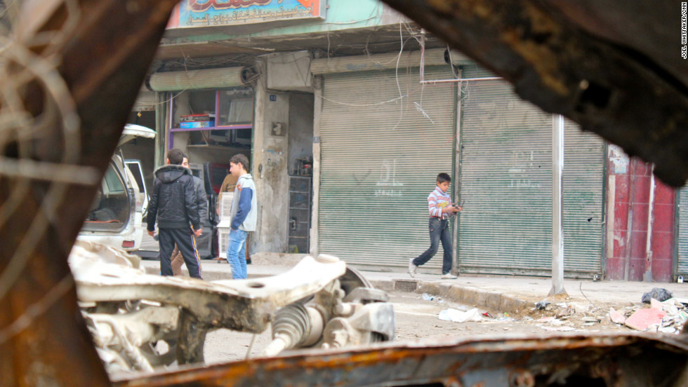 Boys walk through a damaged area In Aleppo, Syria, seen through a destroyed car on December 4.