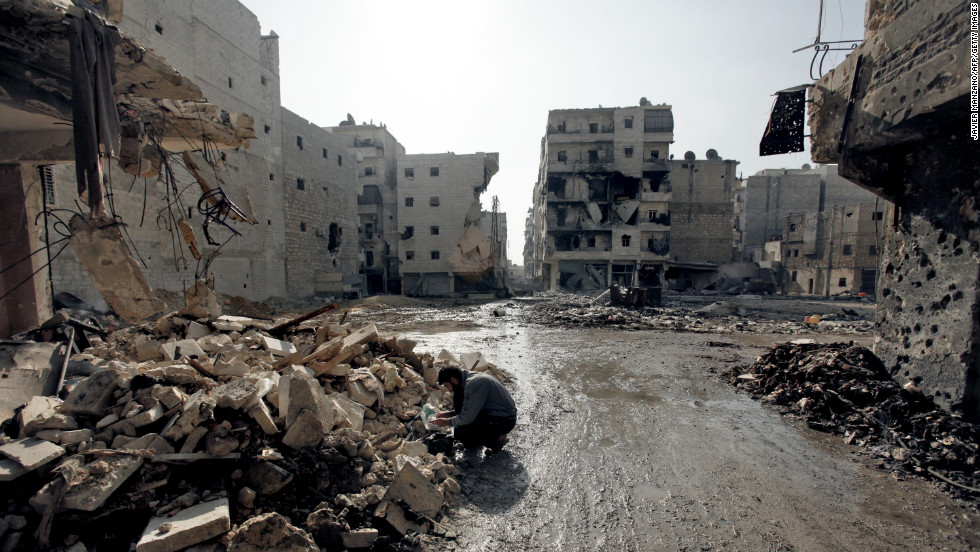 A man inspects rubble in a neighborhood of Aleppo on Sunday, December 2.