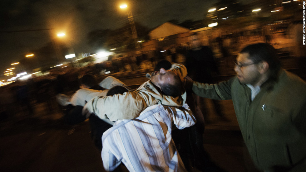 Morsy supporters carry an injured man to safety during clashes with anti-Morsy demonstrators on a road leading to the Egyptian presidential palace on December 5.